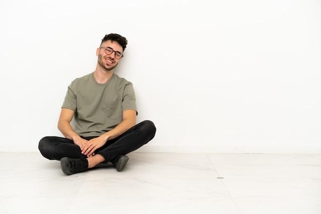 Молодой кавказский человек сидит на полу, изолированные на белом фоне со скрещенными руками и смотрит вперед