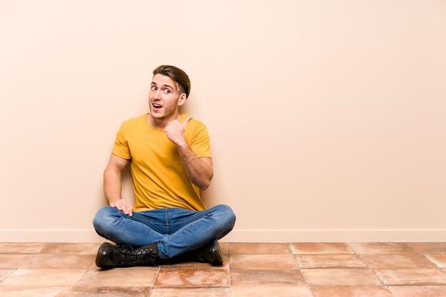 床に座っている若い白人男性は、親指の指を離して、笑ってのんきなポイントを分離しました。