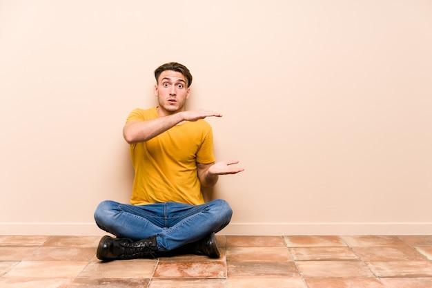 床に座っている若い白人男性は、手の間にコピースペースを持ってショックを受けて驚いた。