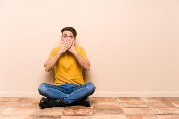 Молодой кавказский человек, сидящий на полу, шокирован, прикрывая рот руками.