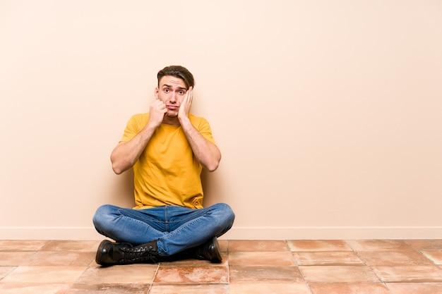 床に座っている若い白人男性は、泣き言を言ったり泣いたりしました。