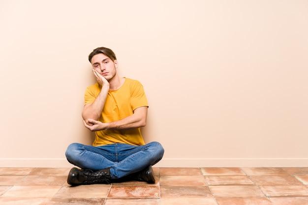 Молодой кавказский человек, сидящий на полу, изолировал себя, которому скучно, устал и нужен день отдыха.