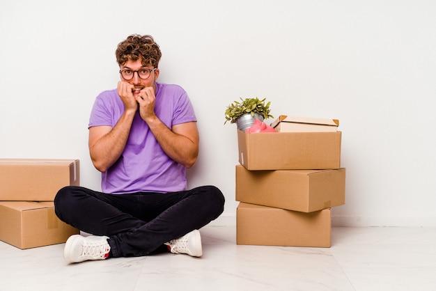 Молодой человек кавказской сидит на полу, готовый к переезду, изолирован на белом фоне, кусая ногти, нервничает и очень тревожится.