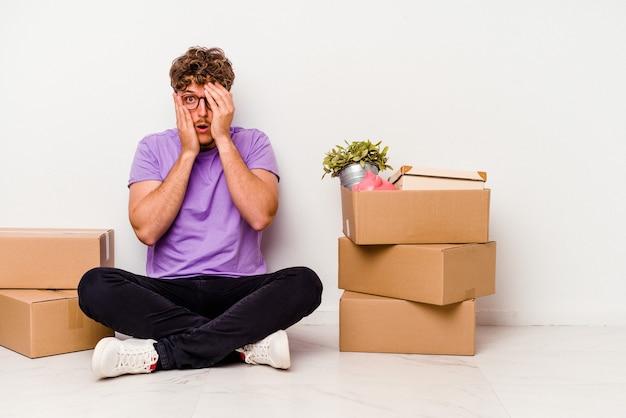 白い背景に孤立して移動する準備ができて床に座っている若い白人男性は、おびえ、神経質な指を点滅します。