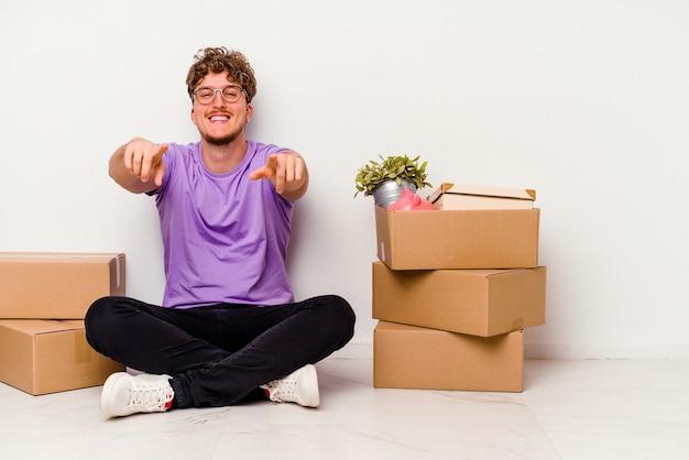 床に座っている若い白人男性が移動する準備ができて、白い背景で隔離の前を向いて陽気な笑顔。