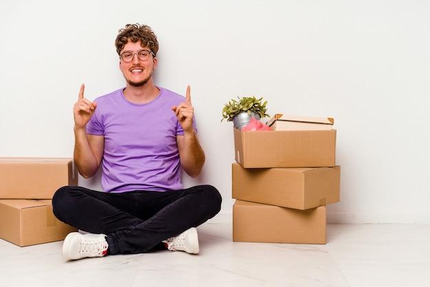 흰색 배경에 고립 이동 준비가 바닥에 앉아 젊은 백인 남자는 빈 공간을 보여주는 두 앞 손가락으로 나타냅니다.