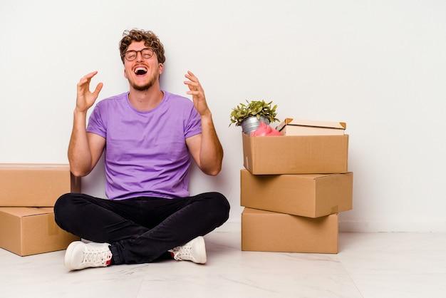 床に座っている若い白人男性は、白い背景に孤立して移動する準備ができて、たくさん笑ってうれしそうです。幸福の概念。