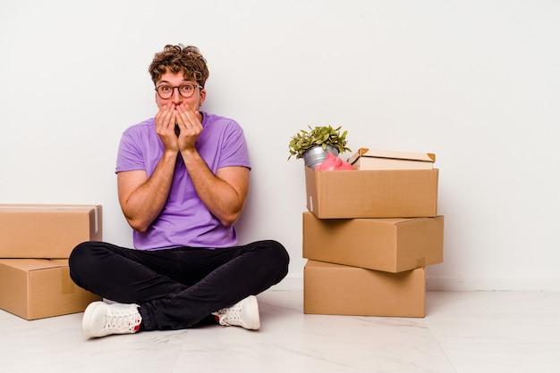 床に座っている若い白人男性は、白い背景で隔離の移動の準備ができて、何かについて笑い、手で口を覆っています。