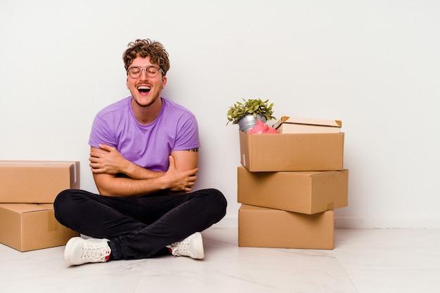 笑って楽しんで白い背景に孤立して移動する準備ができて床に座っている若い白人男性。