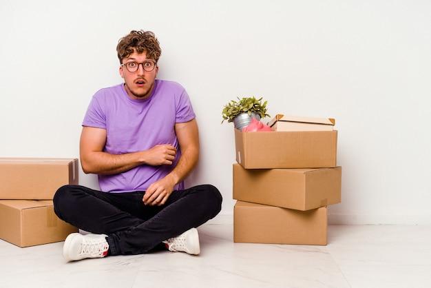 床に座っている若い白人男性は、白い背景に孤立して移動する準備ができて怖くて恐れています。