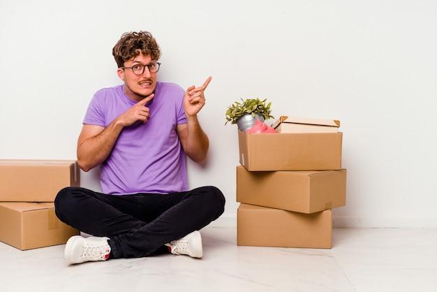 Молодой кавказский человек, сидящий на полу, готовый к переезду, изолирован на белом фоне, потрясен, указывая указательными пальцами на место для копирования.