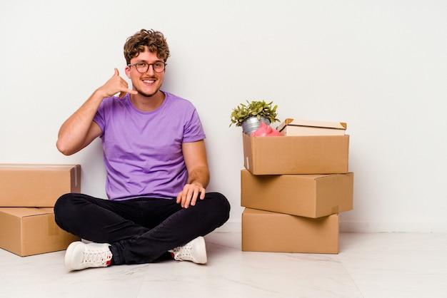 指で携帯電話の呼び出しジェスチャーを示す白い背景で隔離の移動の準備ができて床に座っている若い白人男性。