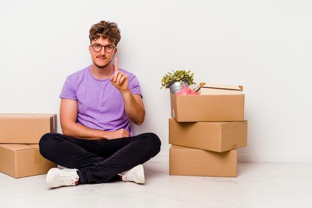 移動の準備ができて床に座っている若い白人男性が指で 1 番を示す白い背景に分離されました。