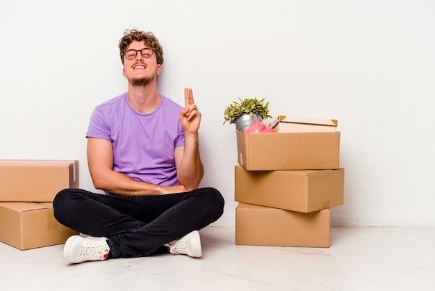 指で2番目を示す白い背景で隔離の移動の準備ができて床に座っている若い白人男性。