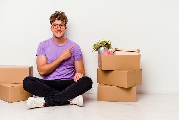 床に座っている若い白人男性は、白い背景に分離された移動の準備ができて、笑顔でわきを指し、空白で何かを示しています。