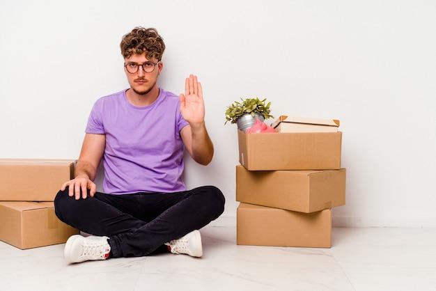 床に座っている若い白人男性は、一時停止の標識を示す差し出された手を伸ばして立っている白い背景に隔離された移動の準備ができて、あなたを防ぎます。