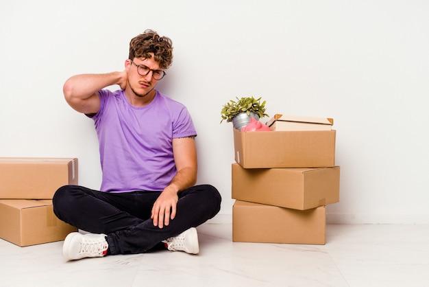 Молодой кавказский человек сидит на полу, готовый к переезду, изолирован на белом фоне и страдает от боли в шее из-за малоподвижного образа жизни.