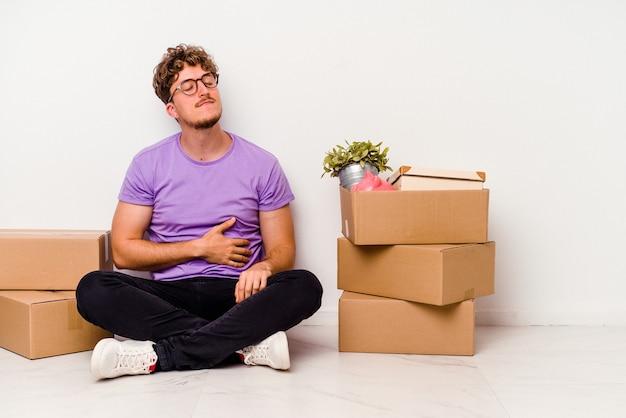 白い背景で隔離の移動の準備ができて床に座っている若い白人男性はおなかに触れ、優しく微笑んで、食事と満足の概念。
