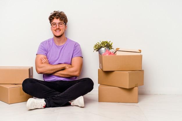 自信を持って、決意を持って腕を組んで、白い背景に孤立して移動する準備ができて床に座っている若い白人男性。