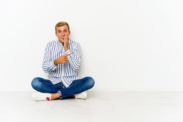 젊은 백인 남자는 험담을 말하고 바닥에 앉아 뭔가보고 측면을 가리키는.