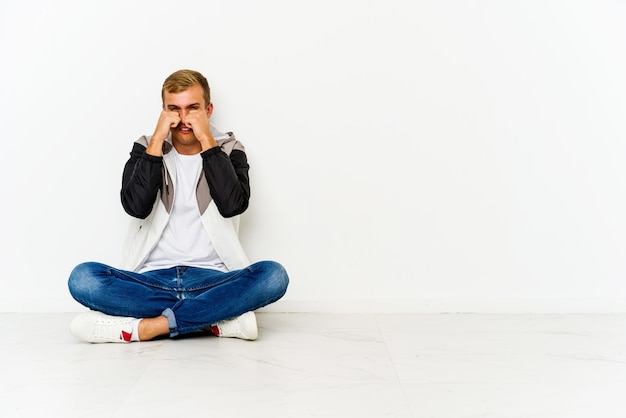 Молодой человек кавказской сидит на полу, ноет и безутешно плачет.