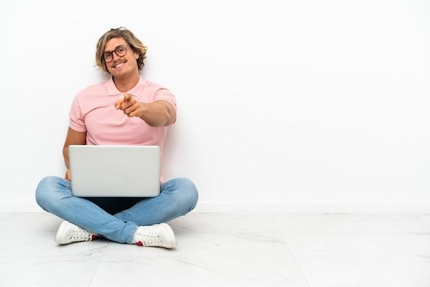행복 한 표정으로 앞을 가리키는 흰색 배경에 고립 된 그의 노트북과 함께 바닥에 앉아 젊은 백인 남자