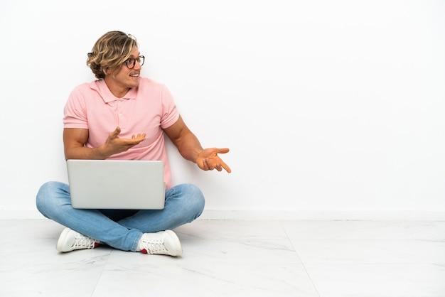 측면을 보면서 놀라운 표정으로 흰색 배경에 고립 된 자신의 노트북과 함께 바닥에 앉아 젊은 백인 남자