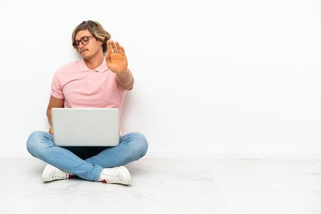 Молодой кавказский человек сидит на полу со своим изолированным ноутбуком