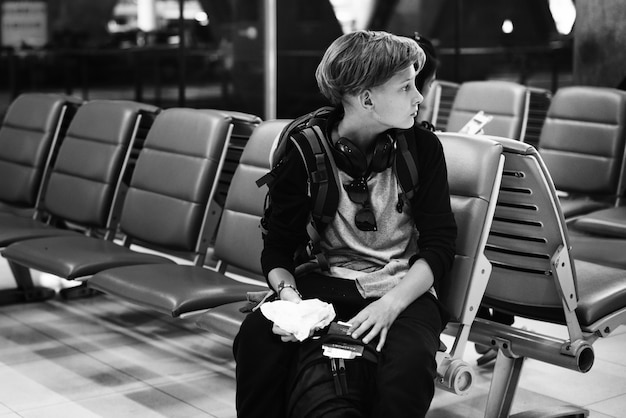 Young caucasian man sitting waiting at airport grayscale