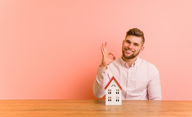 Young caucasian man sitting with a house icon cheerful and confident showing ok gesture.