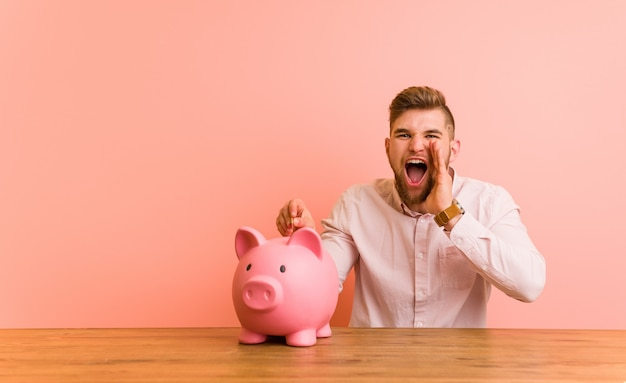 Young caucasian man sitting with a piggy bank shouting excited to front.