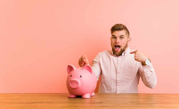 Young caucasian man sitting with a piggy bank surprised pointing at himself, smiling broadly.