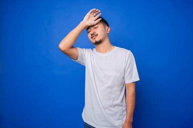 Молодой кавказский мужчина хлопает по лбу, забывая что-то изолированное на синем фоне