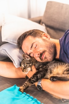 A young caucasian man sleeping on the sofa with his best friend the cat, housemate the precious animal.