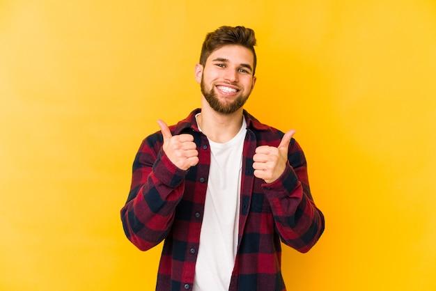 若い白人男性の笑顔と親指を上げる