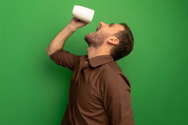 머리 위에 차 한잔 들고 프로필보기에 서있는 젊은 백인 남자는 복사 공간이 녹색 배경에 고립 된 찾고 그것을 마시려고
