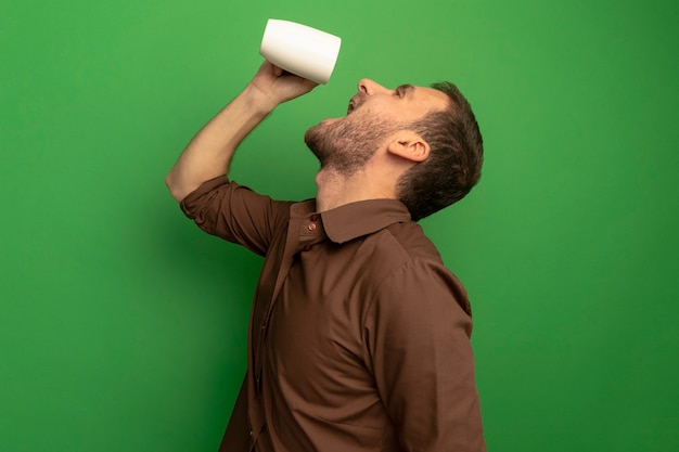 Young caucasian man standing in profile view holding cup of tea above head trying to drink it looking up isolated on green background with copy space