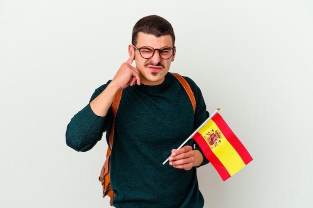 Молодой кавказский человек, изучающий английский язык, изолированные на белом стенном покрытии ушей руками.