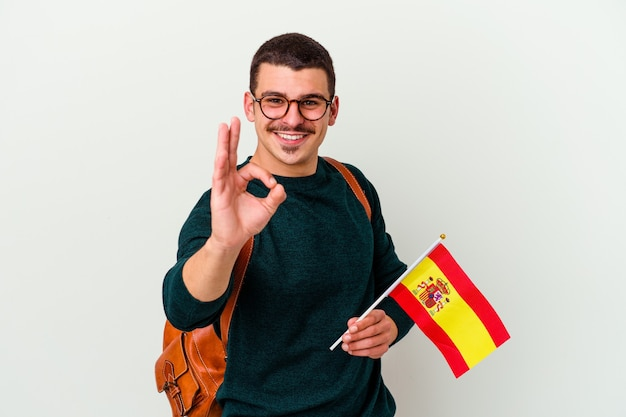 Young caucasian man studying english isolated on white background cheerful and confident showing ok gesture.