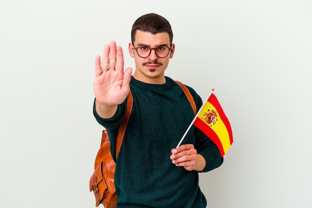 Young caucasian man studying english isolated on white background standing with outstretched hand showing stop sign, preventing you.