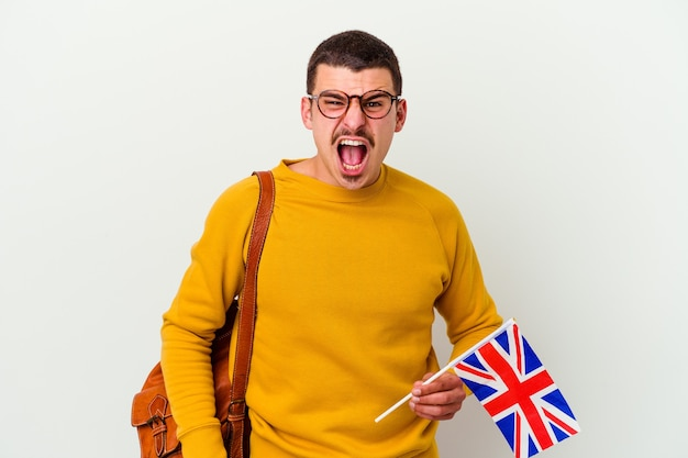 Young caucasian man studying english isolated on white wall screaming very angry and aggressive.