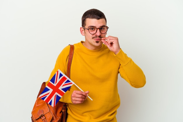 Young caucasian man studying english on white with fingers on lips keeping a secret.