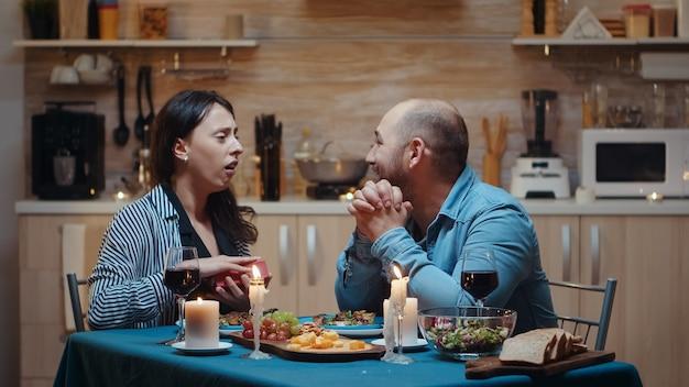 젊은 백인 남자는 부엌에 있는 테이블에 앉아 축제 저녁 식사 중에 선물을 가진 놀라운 여자. 행복한 쾌활한 커플이 집에서 함께 식사를 하고 기념일을 축하하는 식사를 즐깁니다
