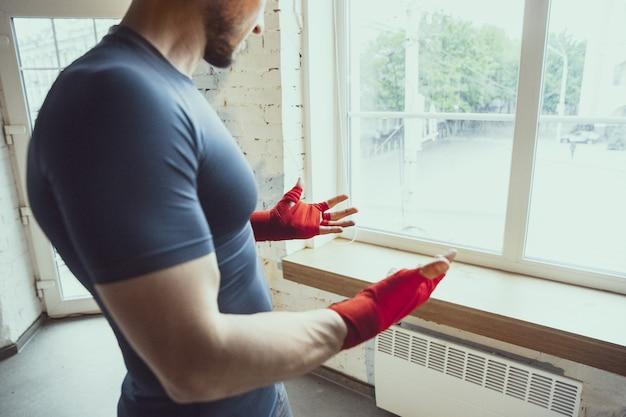 コロナウイルスの検疫中に自宅で訓練している若い白人男性
