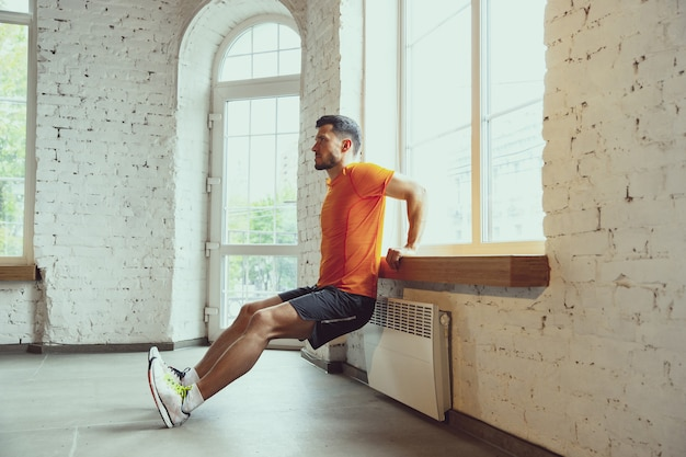 検疫中に自宅でトレーニングしている若い白人男性
