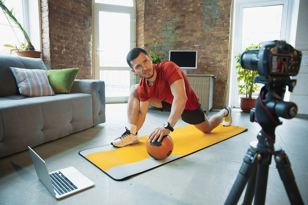 Young caucasian man training at home during quarantine of coronavirus outbreak, doing exercises of fitness