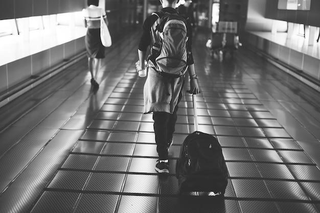 Молодой кавказский мужчина путешествует с багажом в аэропорту