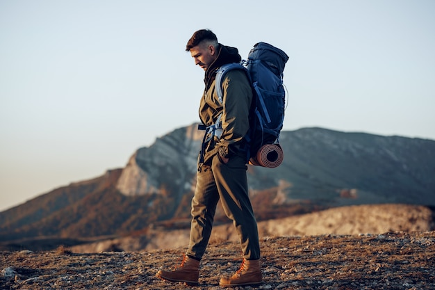 Young caucasian man traveler with big backpack hiking in the mountains