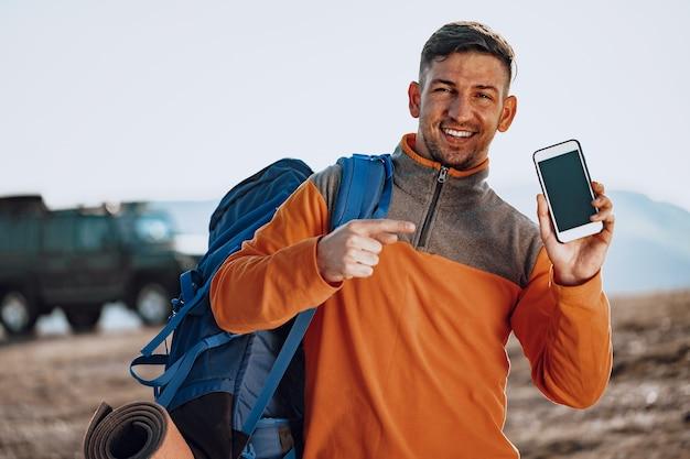 그의 스마트 폰을 사용 하여 젊은 백인 남자 여행자