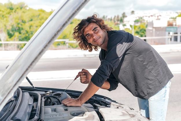 차를 수리하려고하는 젊은 백인 남자